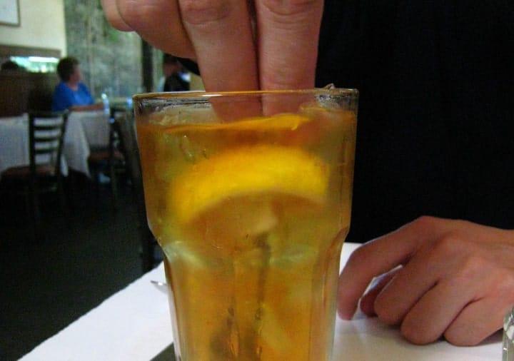 adding lemon slices to tea