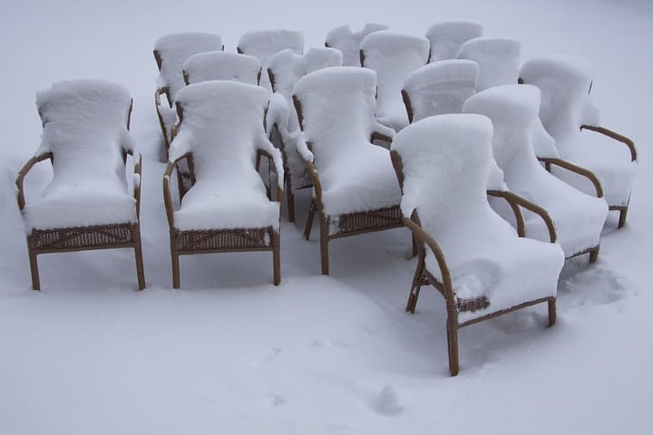 rattan furniture covered in snow