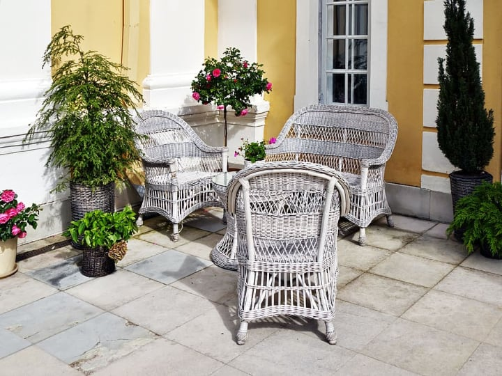 rattan garden furniture surrounded by plants