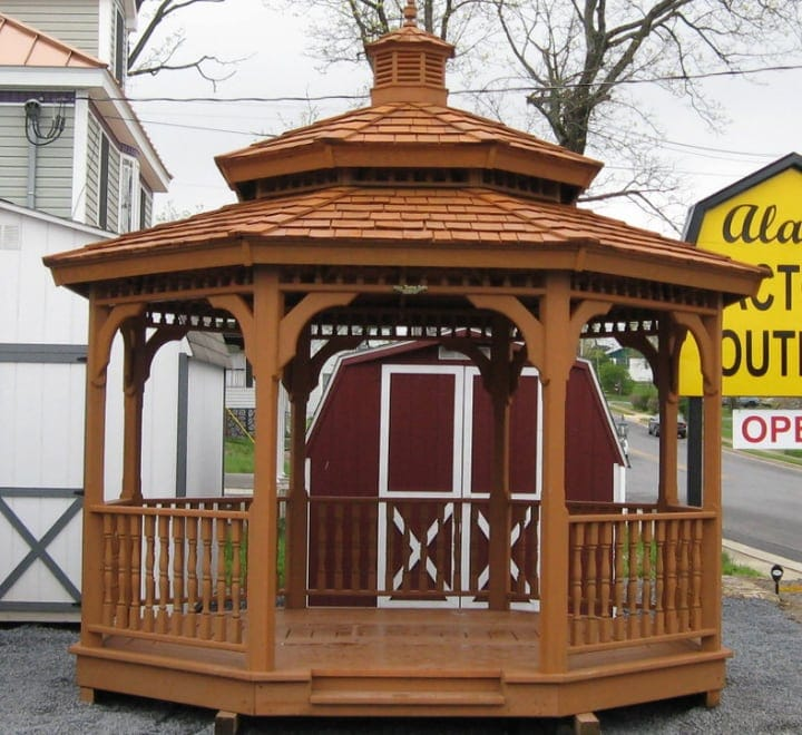 wood gazebo in front of a red barn