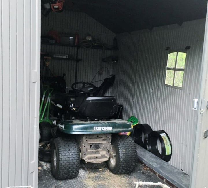 garden shed with wheel lawn mower inside