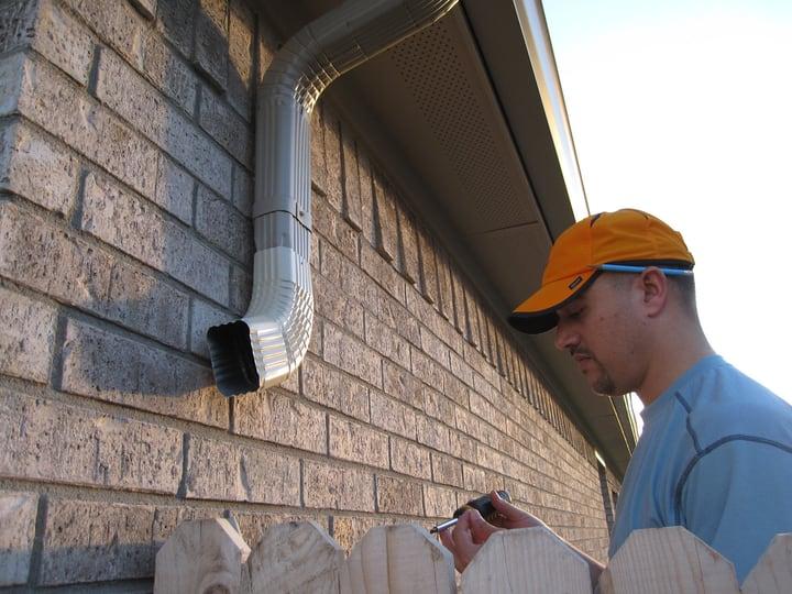 installing rain gutter downspout