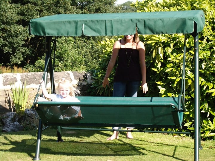 green metal garden swing with a canopy