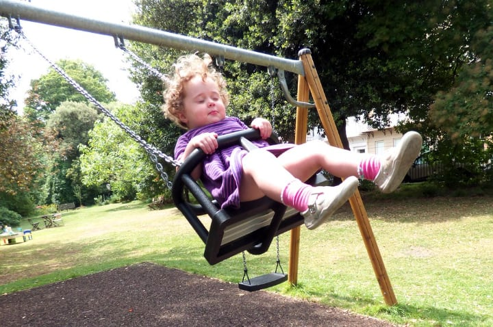 toddler enjoying a ride on a plastic swing