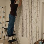 using a step ladder to install wallpaper