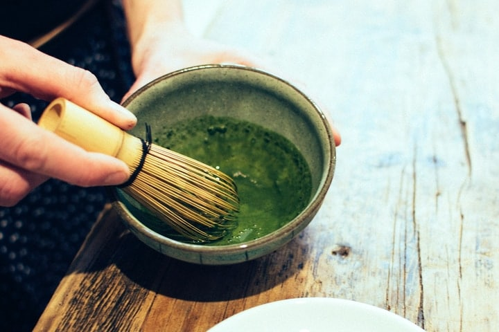 whisking the matcha green tea