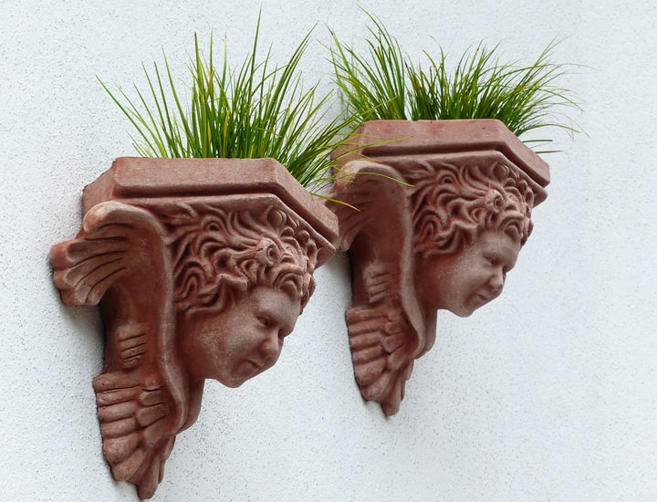 sculpture planters on white wall garden